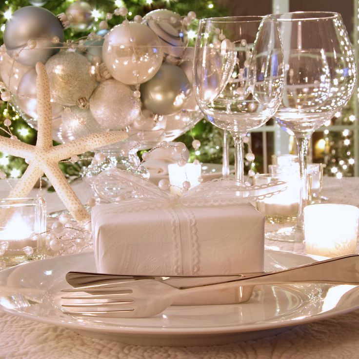 Elegantly lit  holiday dinner table with wine glasses and white ribboned gift