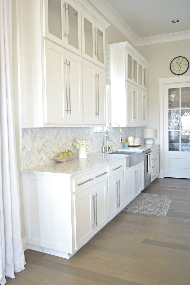 white-kitchen-stainless-farmhouse-sink-herringbone-backsplash-carriara-marble-counter-tops