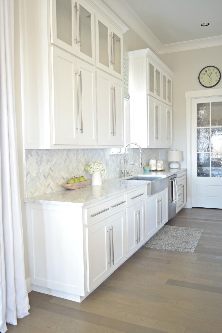 white-kitchen-stainless-farmhouse-sink-herringbone-backsplash-carriara-marble-counter-tops